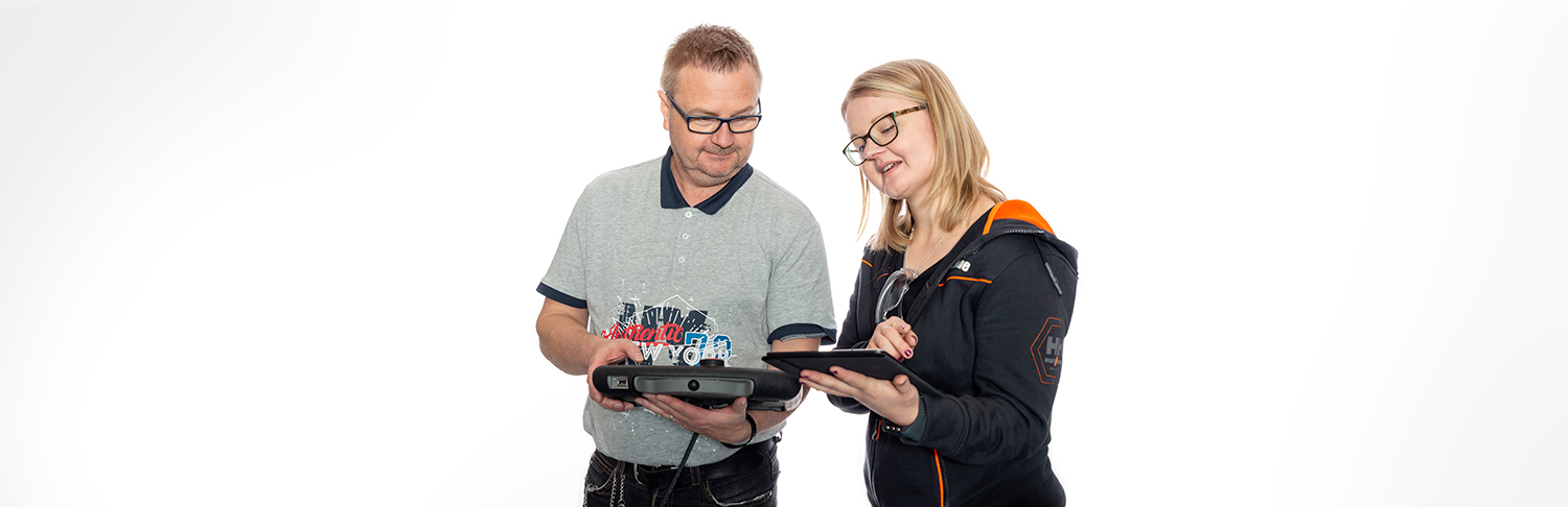 Two people learning how to control a cobot with digital instructional materials.